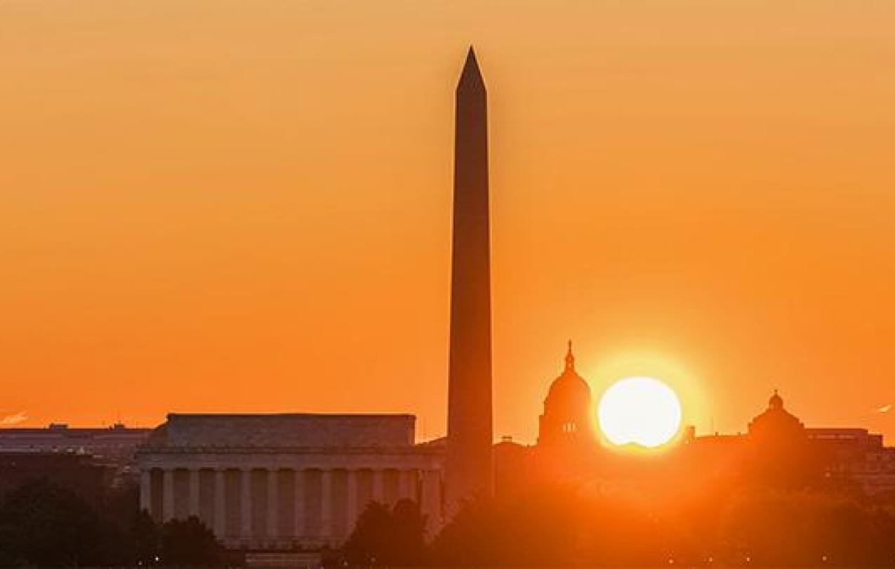 The sun sets over the Washington Memorial in Washington, D.C.